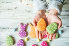 Multicolored gingerbread cookies in the shape of bunnies and decorated eggs on a white wooden textural background. Kids hands hold. Ing homemade gingerbread royalty free stock images