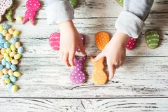 Multicolored gingerbread cookies in the shape of bunnies and decorated eggs on a white wooden textural background. Kids hands hold. Ing homemade gingerbread stock image