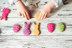 Multicolored gingerbread cookies in the shape of bunnies and decorated eggs on a white wooden textural background. Kids hands hold. Ing homemade gingerbread stock photography