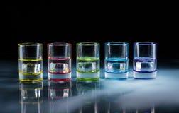 Multicolored glazen die met alcoholische dranken, met binnen ijsblokjes worden gevuld die, zich op de spiegeloppervlakte bevinden stock afbeeldingen