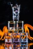 Multicolored glazen die met alcoholische dranken, met splases die van ijsblokjes worden gevuld die binnen vallen, op de spiegelop stock foto's