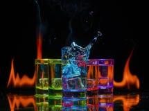 Multicolored glazen die met alcoholische dranken, met splases die van ijsblokjes worden gevuld die binnen vallen, op de spiegelop royalty-vrije stock afbeelding