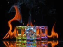 Multicolored glazen die met alcoholische dranken, met splases die van ijsblokjes worden gevuld die binnen vallen, op de spiegelop royalty-vrije stock foto