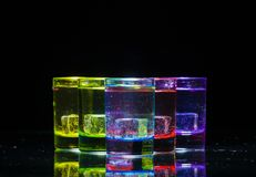 Multicolored glazen met alcoholische dranken, met binnen ijsblokjes worden gevuld die, zich op de spiegeloppervlakte die bevinden stock afbeeldingen