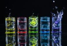 Multicolored glazen met alcoholische dranken, met splases die van ijsblokjes worden gevuld die binnen vallen, zich op de spiegelo royalty-vrije stock afbeelding