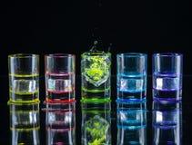 Multicolored glazen met alcoholische dranken, met splases die van ijsblokjes worden gevuld die binnen vallen, zich op de spiegelo stock foto's