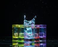 Multicolored glazen met alcoholische dranken, met splases die van ijsblokjes worden gevuld die binnen vallen, zich op de spiegelo stock afbeeldingen