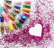 Multicolored glitter in bottles makeup place for text in heart Stock Image