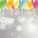 Multicolored glossy balloons on a silver festive background Stock Images