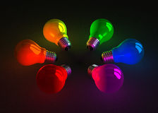 Multicolored glowing light bulbs lying on dark Stock Photos