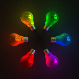 Multicolored glowing light bulbs lying on dark Stock Photography