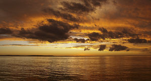 Multicolored golden sunrise over water. Gold,orange and black colors in sunrise through Cumulus and Stratocumulus clouds.This photo was taken in Tin Can Bay Royalty Free Stock Images