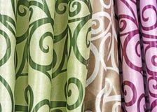 Multicolored gordijnontwerpen in een detailhandelvenster Steekproeven van de textuur van multi-colored stoffen stock afbeeldingen