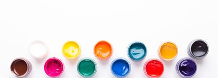 Multicolored gouache on a white background Isolated Paints in containers Top view Banner Horizontal stock photography