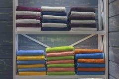 Multicolored handdoeken zijn op de plank stock afbeeldingen