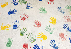 Multicolored handprints on the white wall Stock Photos