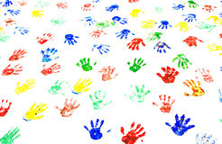 Multicolored handprints on the white wall Stock Photo