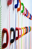 Multicolored handsets with spring wire spiralon a white wall. Stock Images