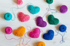 Multicolored Hearts with a balls of thread on white wooden backg Royalty Free Stock Photos