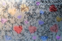 Multicolored hearts background. Multicolored hearts on frosty patterns of window glass stock image
