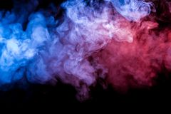 Multicolored heavy smoke from a vape of blue and purple color of the exhaled by scattered by clubs on a black isolated background stock photo