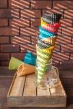 Multicolored hoornen voor roomijs in een kruik bevinden zich op een houten doos in een tegenover elkaar stellend schaduwpatroon v stock fotografie