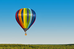 Multicolored hot air balloon flying over a forest Stock Photo