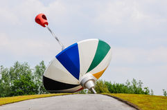 Multicolored humming top made ​​of stainless steel. Colorful art work of the Dutch designer Piet Hohmann (1935) situated on a roundabout in the stock images