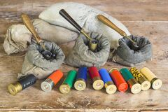 Multicolored hunting cartridges and many different bags with lead fractions and measure tools on old wooden background