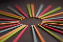 Multicolored Indian incense sticks lie in the shape of sun and rays on a brown background, with empty circle, side view royalty free stock photos