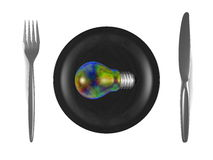 Multicolored iridescent light bulb, black plate, steel fork and knife. Top view Stock Image