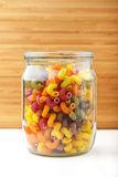 Multicolored Italian pasta in a jar. Colored pasta in a jar and some scattered on the white wooden table, vertical photo Royalty Free Stock Photo