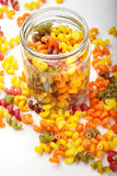 Multicolored Italian pasta in a jar. Colored pasta in a jar and some scattered on the white wooden table, vertical photo Stock Images