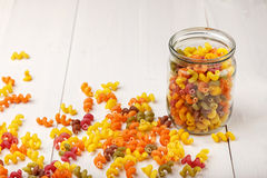 Multicolored Italian pasta in a jar. And some scattered on the white wooden table, horizontal photo Royalty Free Stock Photography