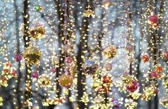Multicolored Kerstmisballen en slingers die op de straat hangen stock afbeelding