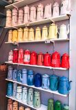 Multicolored kettles collection lined up on shelves royalty free stock photos