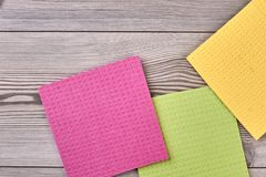 Multicolored kitchen cleaning napkin rags. Cellulose sponge kitchen objects on the wood texture background, copy space stock photo
