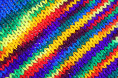 Multicolored knitting. A winter scarf knitted from multicolored wool Stock Photos