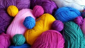 Multicolored knitting yarn. Knitting yarn in rainbow colors on a dark wooden background Royalty Free Stock Photography