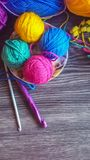 Multicolored knitting yarn. Knitting yarn in rainbow colors on a dark wooden background Stock Photography
