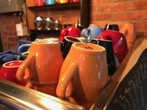 Multicolored koffie en theekoppen op een koffiemachine tegen een bakstenen muur worden gevestigd die royalty-vrije stock afbeelding