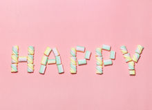 Multicolored letters HAPPY from marshmallow on gentle pink background. Flat lay. Image for valentine day concept Stock Photo