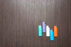 Multicolored lighters on a dark wooden table royalty free stock images