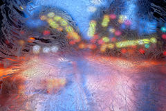 Multicolored lights of the city behind frosty glass with frosty patterns Royalty Free Stock Image