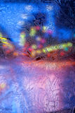 Multicolored lights of the city behind frosty glass with frosty patterns Royalty Free Stock Images