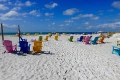 Multicolored ligstoelen op een wit strand, die de oceaan onder ogen zien Stock Afbeelding