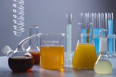 Multicolored liquids in laboratory containers. Multicolored liquids in laboratory glassware on a gray background Stock Images