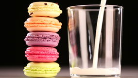 Multicolored macaron and pouring milk stock video