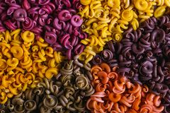 Multicolored macaroni of unusual shape with natural vegetable dyes, lined in a circle. Background closeup stock photos