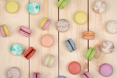 Multicolored macarons. A lot of multicolored macarons on wooden background Royalty Free Stock Images